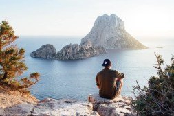 rear-view-of-man-sitting-on-rock-by-sea