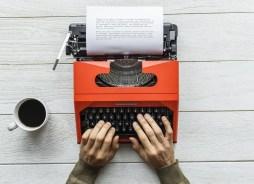 Man typing on a red vintage typewriter-min