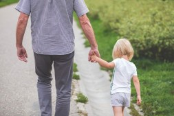 grandpa and grand daughter walking together and holding hands