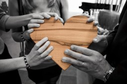adults holding a wooden heart