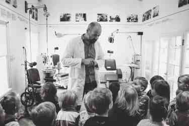 grayscale photo of man lecturing children