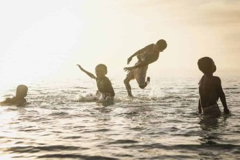 Four kids playing in the ocean during sunset