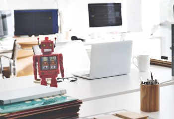 red toy robot at a modern startup workspace