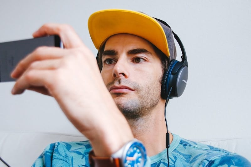 Man Using his smartphone to watch a Youtube Video