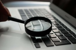 Magnifying Glass Used to Look at a Keyboard of a Laptop