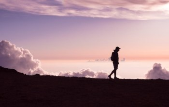 Man Walking on top of a mountain during sunset