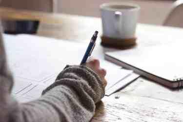 Woman writing an inspirational essay for class