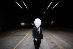 Man Hiding His Face Behind a Balloon