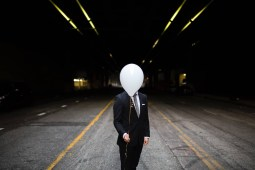 Man Hiding His Face Behind a Balloon