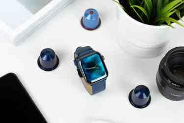 blue watch beside camera lens near plant