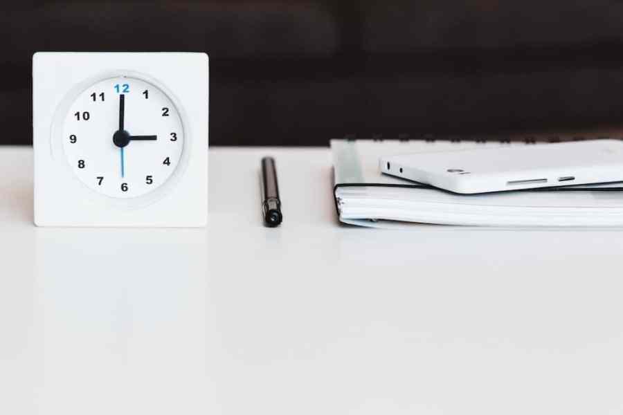 white desk clock near pen and book