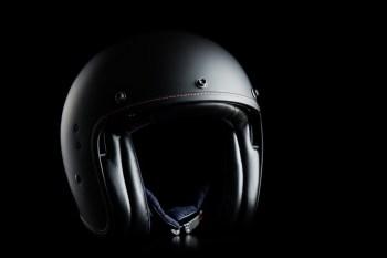 Open face motorcycle helmet on black background.