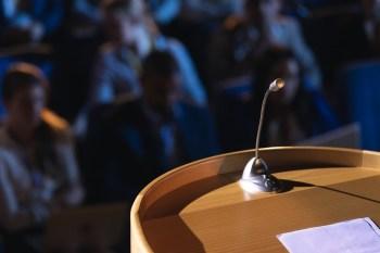 Close up of podium with speaker in auditorium
