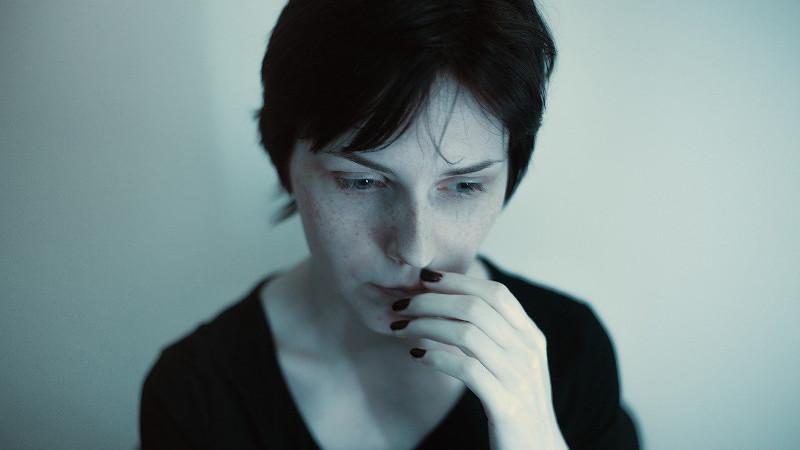 Femme émotive et hypersensible, la main sur le visage