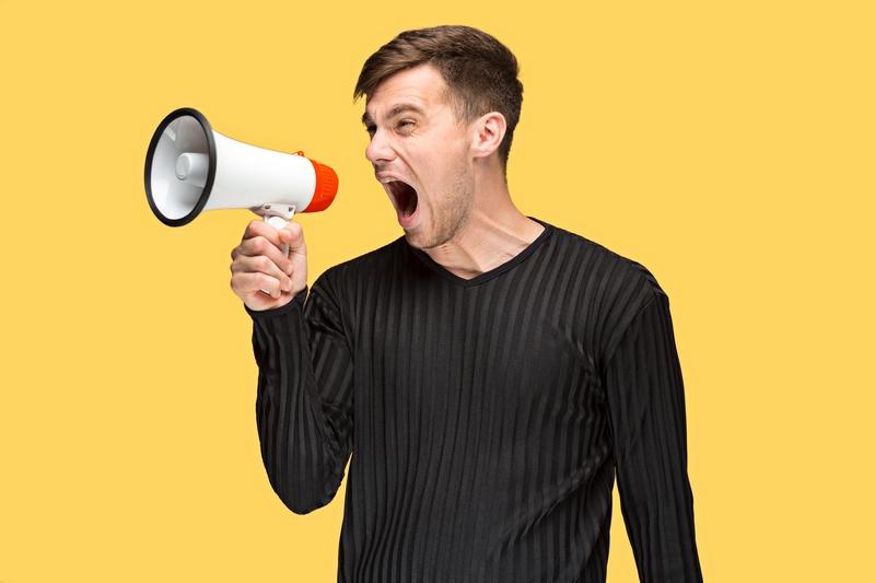 homme qui tient un haut parleur et qui hurle