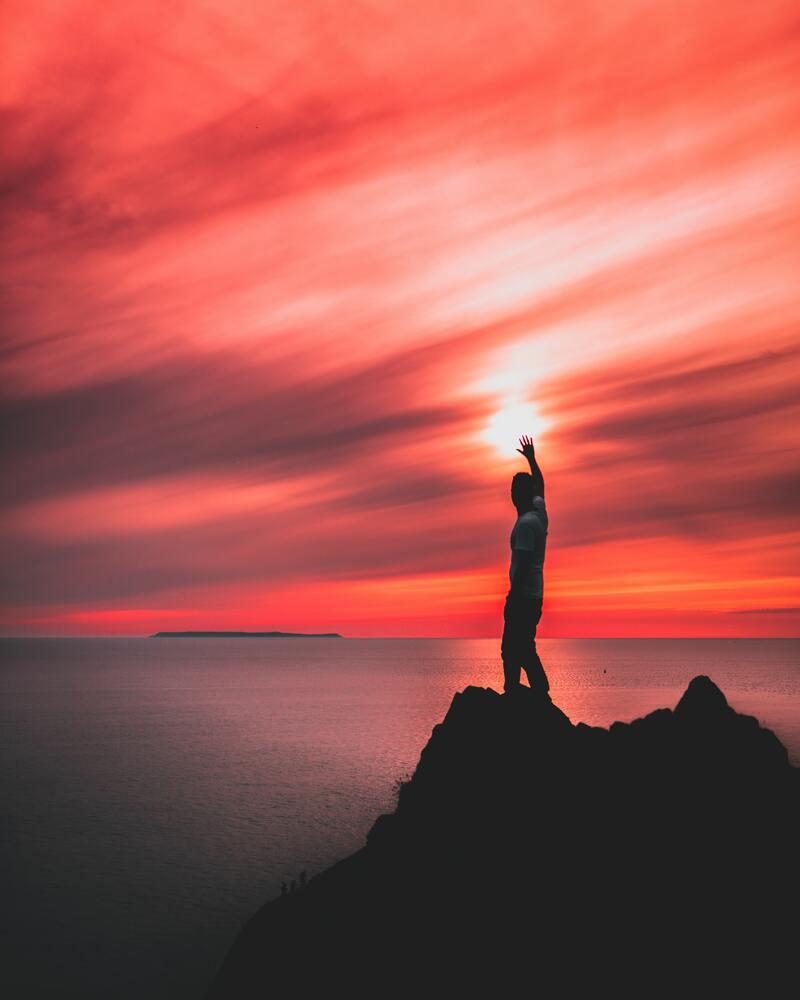 homme sur un rocher qui observe l'horizon et lève le bras