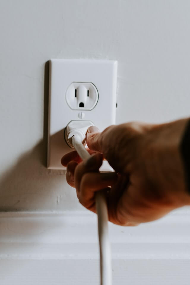 gaining-control-of-your-life-hand-plugging-in-white-electric-plug-white-wall-socket