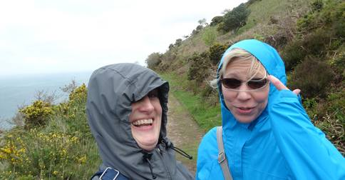 Sara and Julie on windswept cliff.