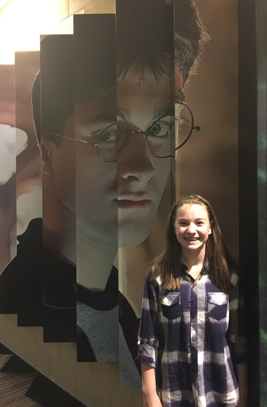 Natalie Bourn Standing in front of the movie character wall at the new Century Arden 14 Theatre in Sacramento