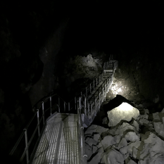 Steel Walkway and Stairs Descending Into The Pitch Black Lava River Cave