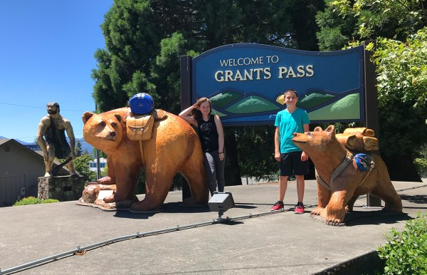 Natalie and Carter Bourn with the Grants Pass Bear and Caveman Statues