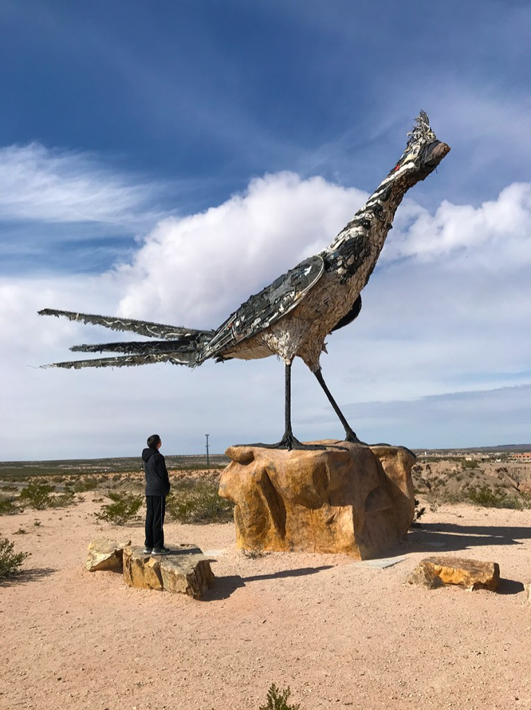 Carter Bourn Looking Up at The Recycled Roadrunner Statue