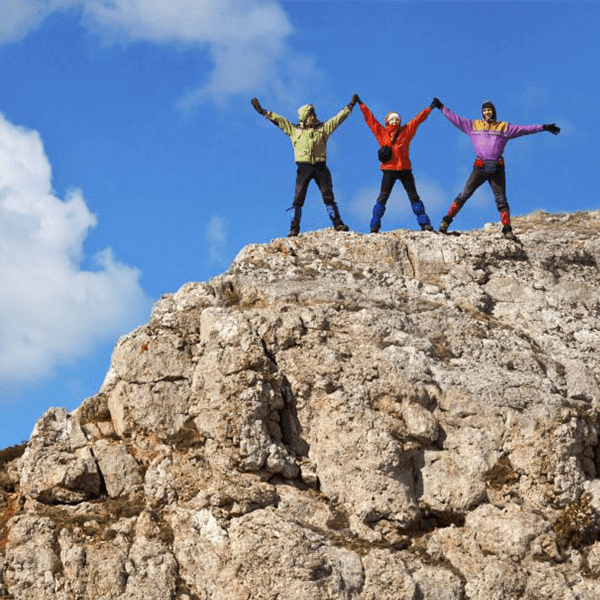 Leadership. Three people on top of cliff