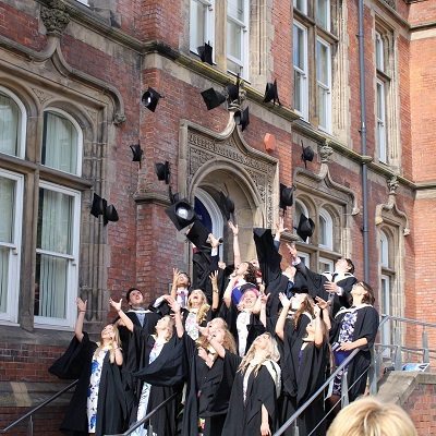 Uni of Sheffield Students throwing graduation caps into the air