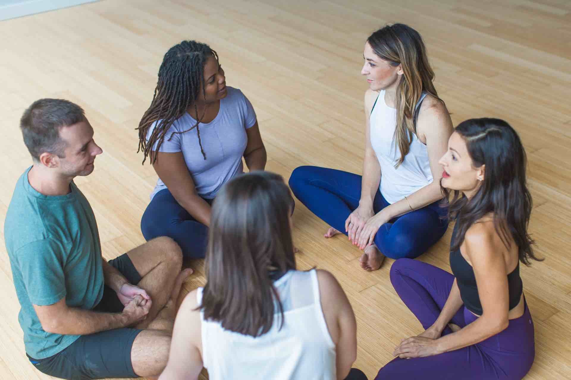 Group of Denton yoga teacher training students discussing materials following yoga classes