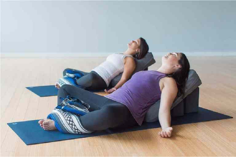 Two students reclined on mat during yin yoga class style