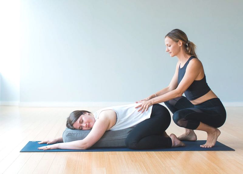 Instructor assisting student yin pose during private lesson