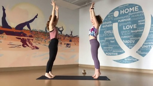 Rachel and her daughter practicing yoga together standing facing each other on yoga mat