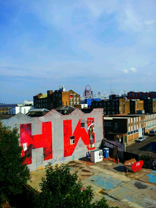 The huge HW was formerly part of a giant Coca Cola mural which once filled the whole wall.  It can be seen from the Hackney Wick Overground station