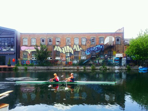 Canoeists on the Lea Navigation with painted warehouses in the background
