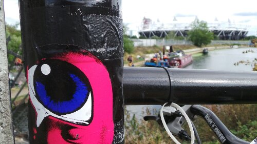 Paul Insect sticker on the towpath of the Lea Navigation with the park in the background