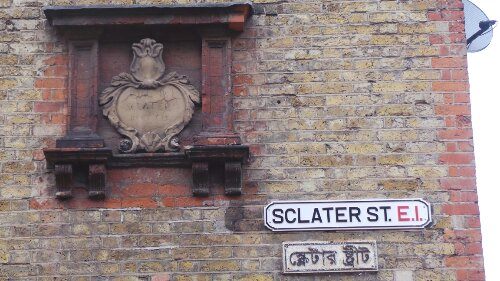 Three different types of signage on Sclater Street. including the original signage and other versions in the languages of the area