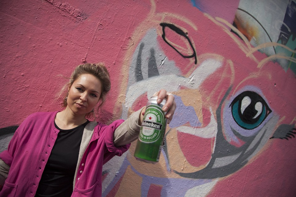 Suzko in front of her big cat mural