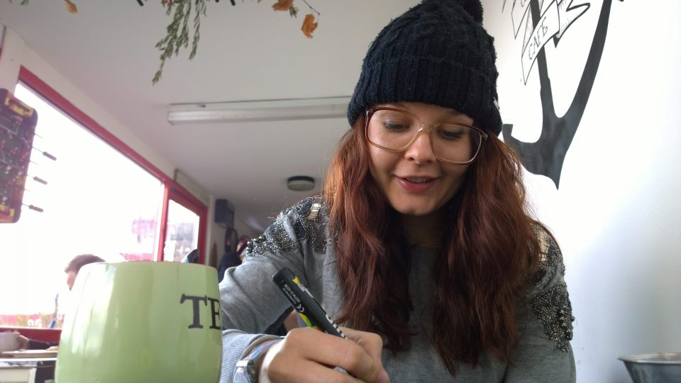 Kayleigh Doughty also known as Artista drawing in the Driftwood Cafe