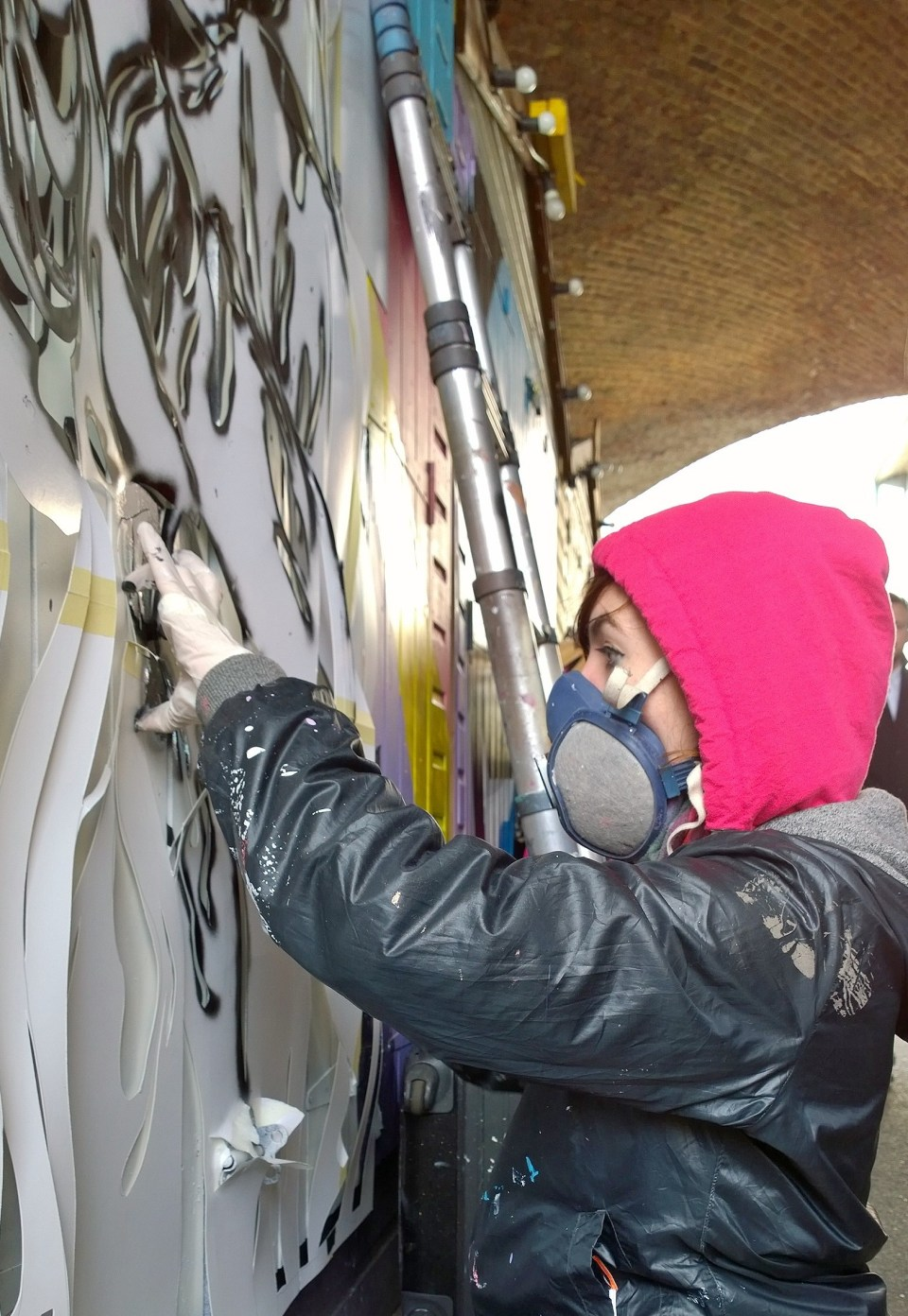 Zabou finishing her mural by adding the all important stencil