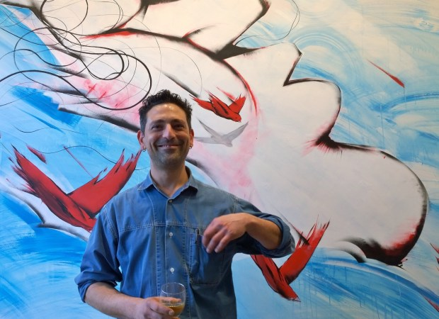 Italian artist RUN next to his artwork at the launch