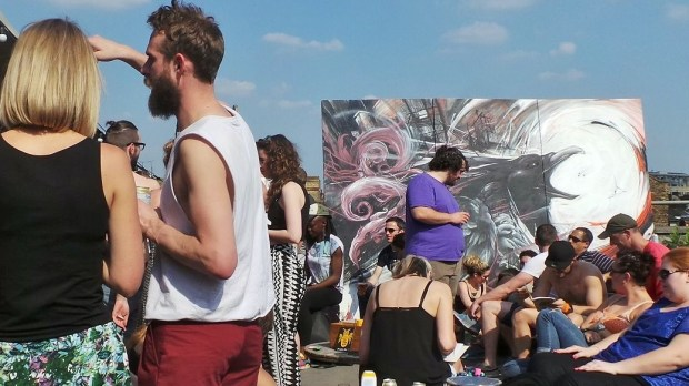 Crowds at the event with art from Zadok in the background
