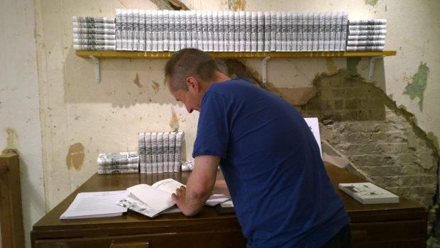 John signing his book
