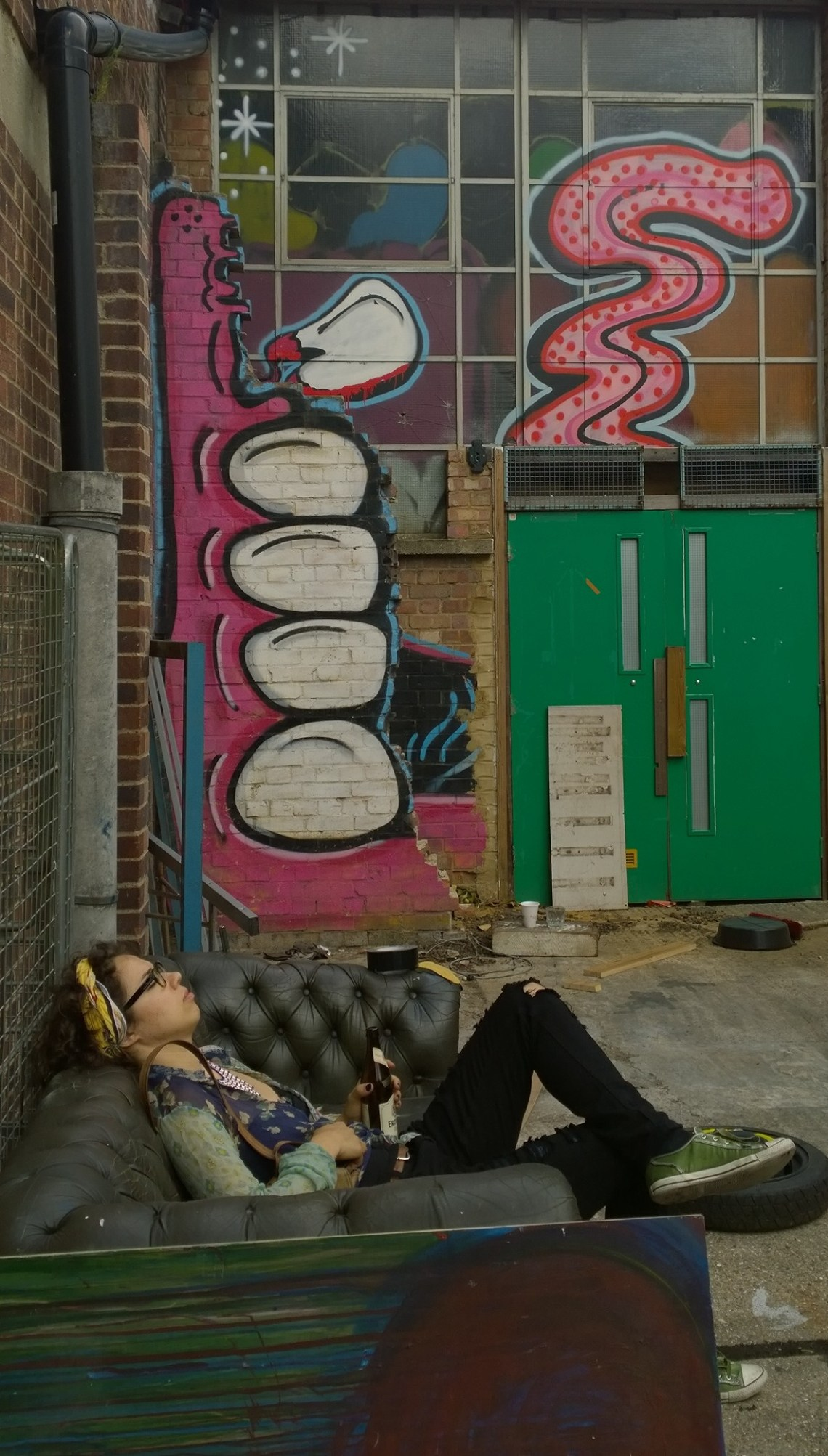 A woman relaxes next to a giant painting from Sweet Toof
