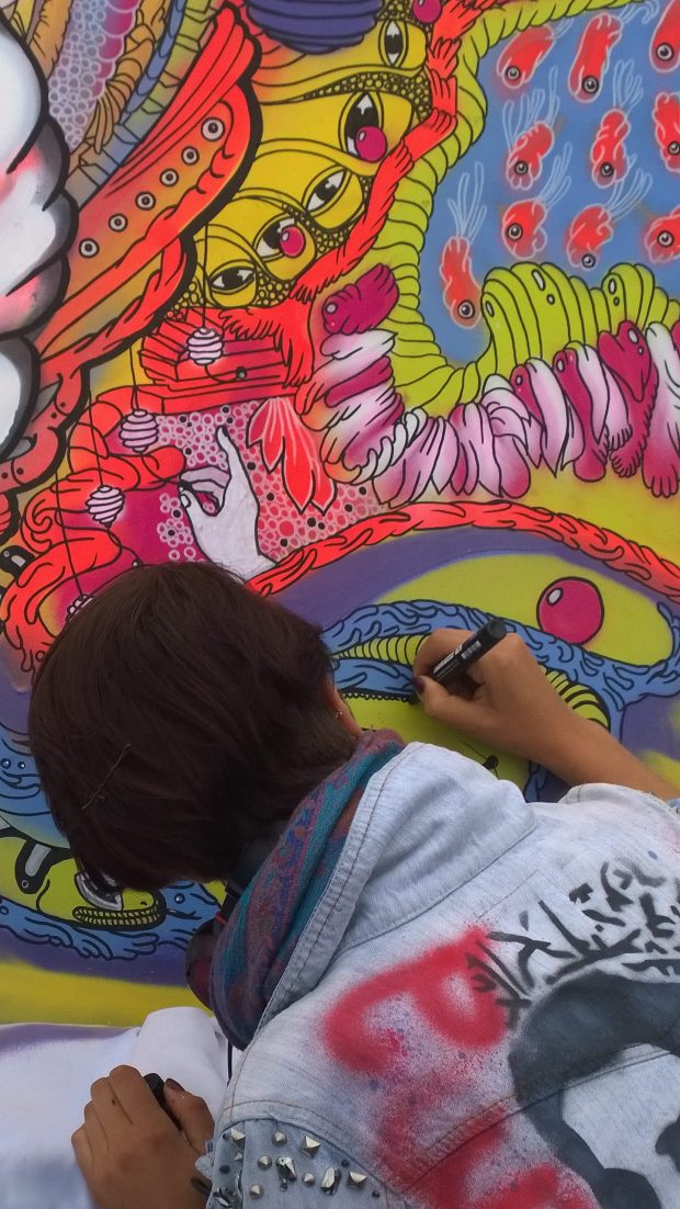 Maggio adding some colouful detail to her painting of the Goddess of Peace on the rooftop