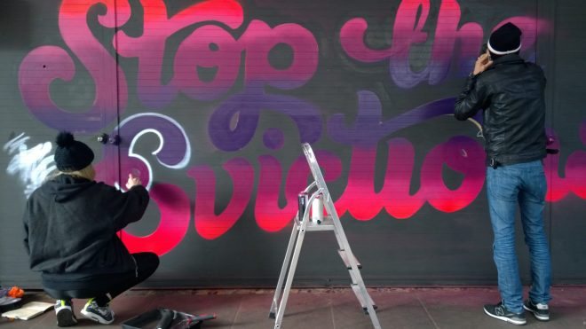 Lilly Lou putting the final touches onto her mural with some help from a friend