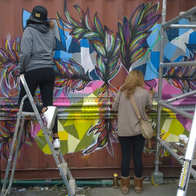 Azarra and friend finishing off her piece