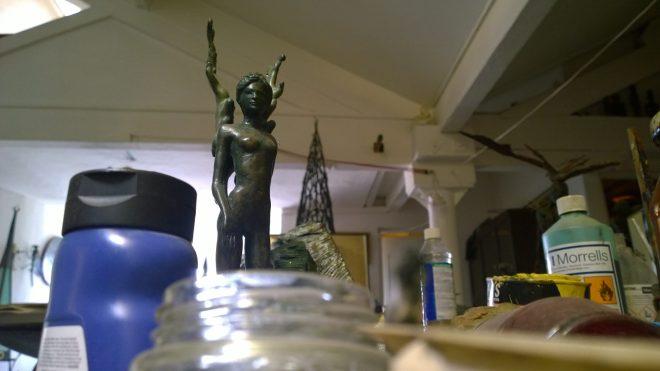 A bronze winged figure overlooking the workshop