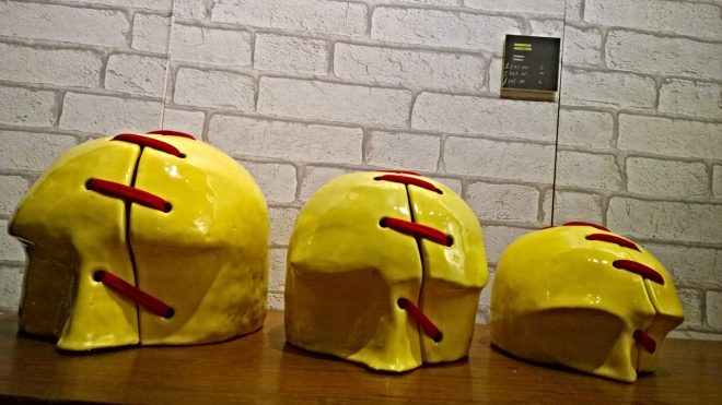 Bright yellow Male skulls held together with a woman's hosiery.