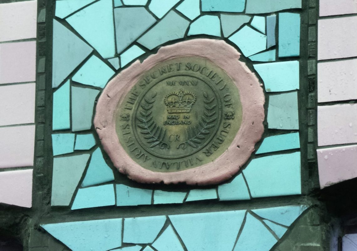 A 'Secret Society of Super Villain Artists' plaque on the front of Carrie Reichardt's mosaic house