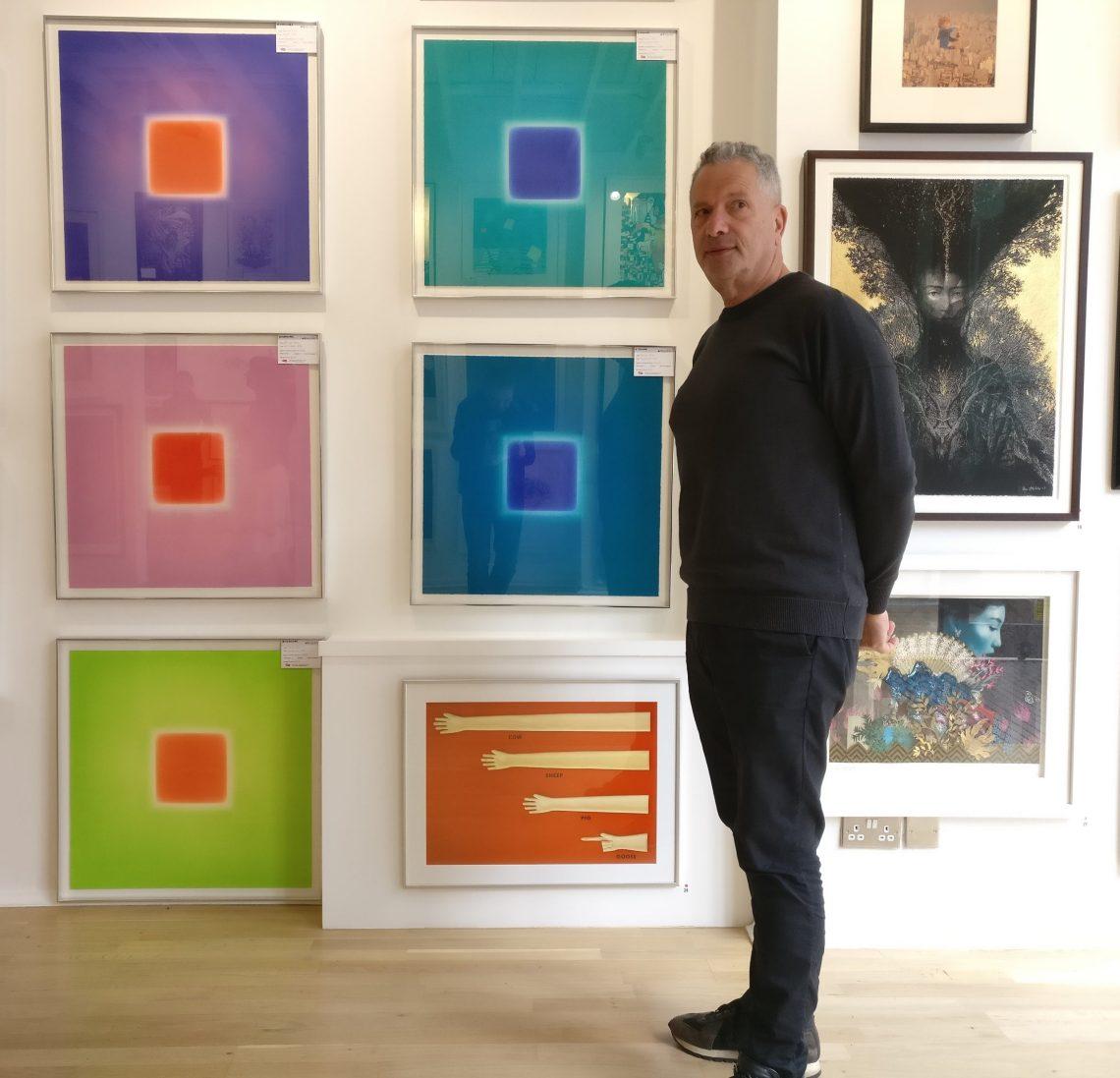 Lawrence Alkin in front of art inside the Art Republic Gallery